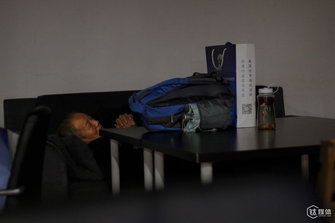 In this café, people can pay only 30 RMB for staying one night on the couch. Wang Xiuli has spent 12 night here, with his belongings, including a backpack, a paper bag, and a kettle, on the desk.