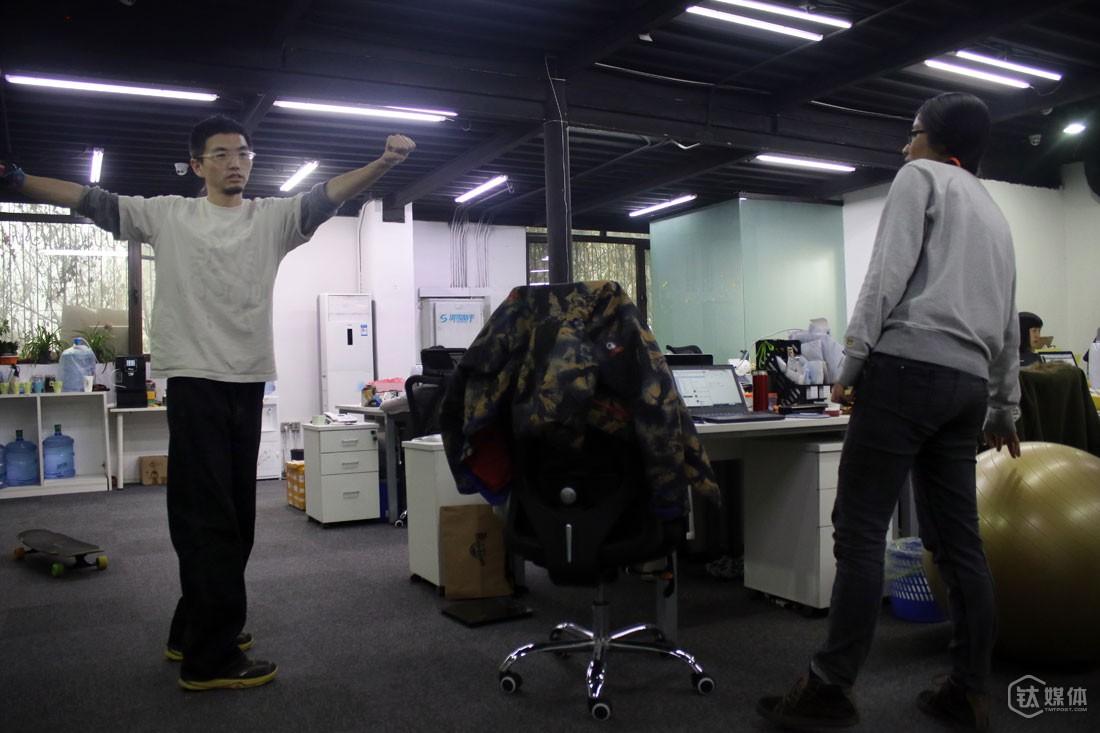 球叔在办公室为同事示范滑雪动作,一些人想找他学滑雪,但他现在基本上没时间做教学了。