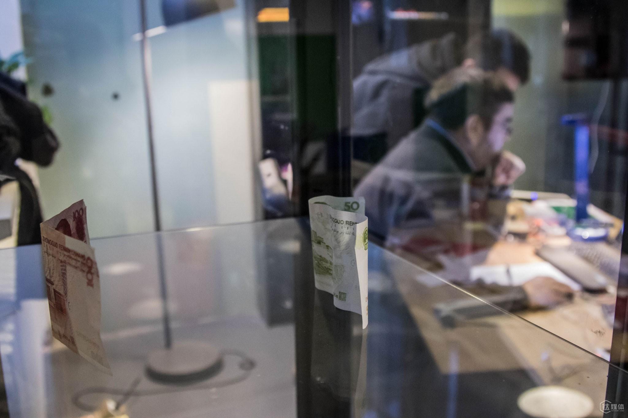 """在这个拥有特殊视角的空间里,托马斯摆了两张假钞。这个陈设源于他5个子女中的一个儿子在北京的一次经历:""""有一回我的一个儿子在北京打车,付车费时司机拿钱看了一下,之后告诉他说'是假钱',那之后,我把这两张钱拿到办公室,放在了陈列柜里"""",托马斯说自己并不是想表达什么,而只是觉得""""这是艺术""""。"""