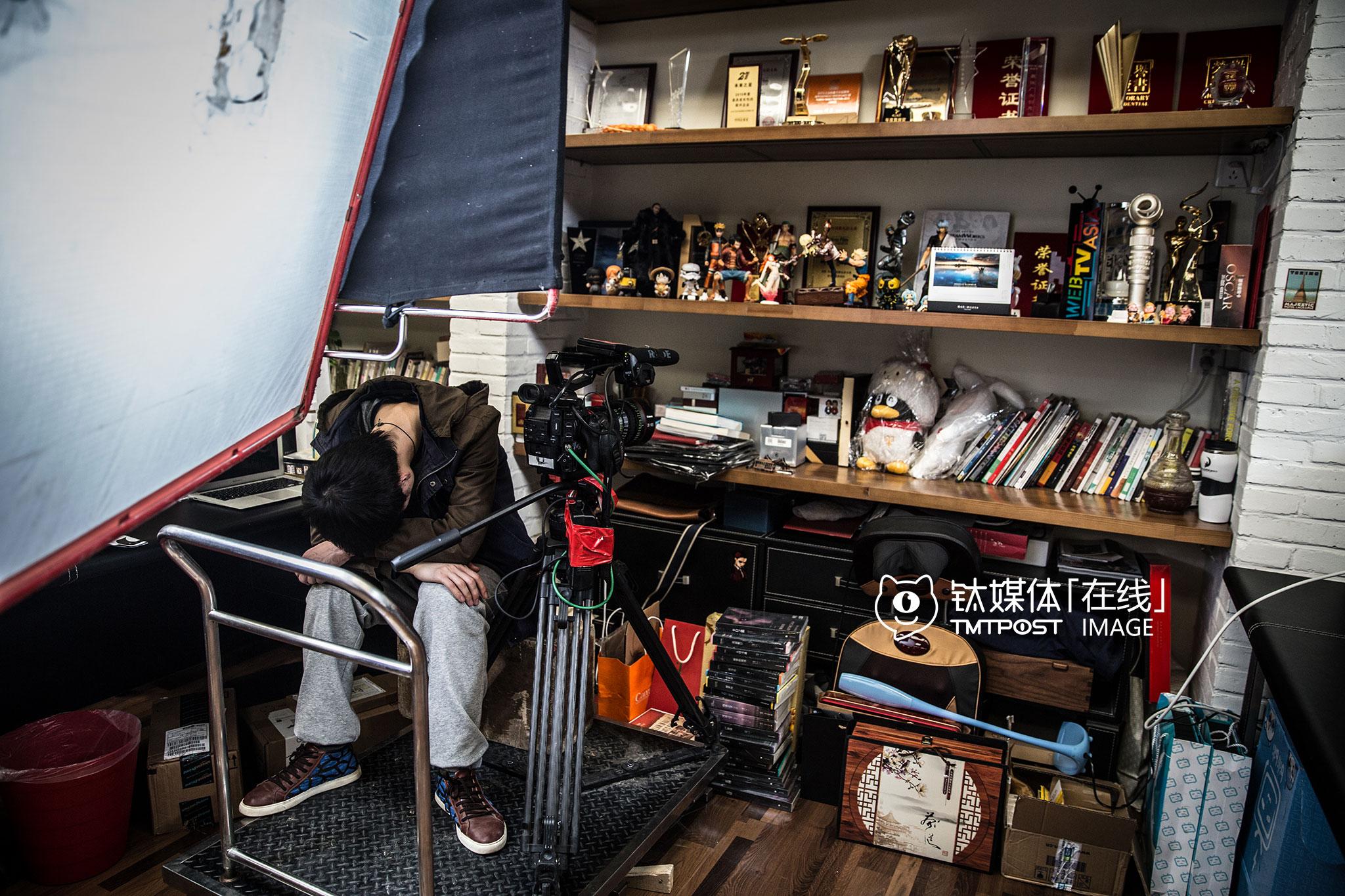 叫兽易小星的办公桌前,一名剧组成员抓住短暂午休时间在休息,书柜上摆满了各种奖项和玩偶。