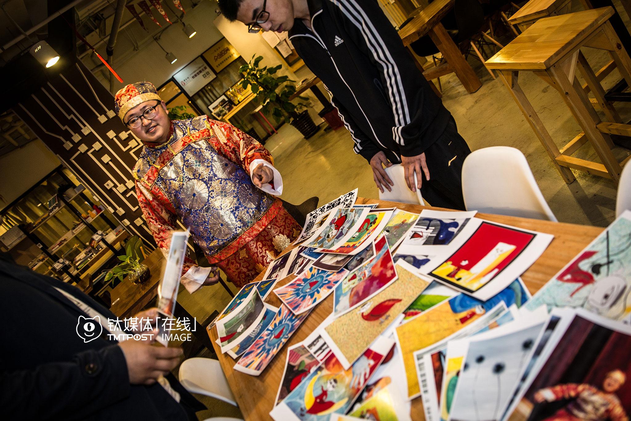 """吴建辉在咖啡馆向别人介绍自己的漫画,这些颇具云南民俗风的作品,引起了不少人的兴趣,""""我在打磨剧本,有些眉目了,现在就想找人一起拍出来,一起来让更多人知道。"""""""