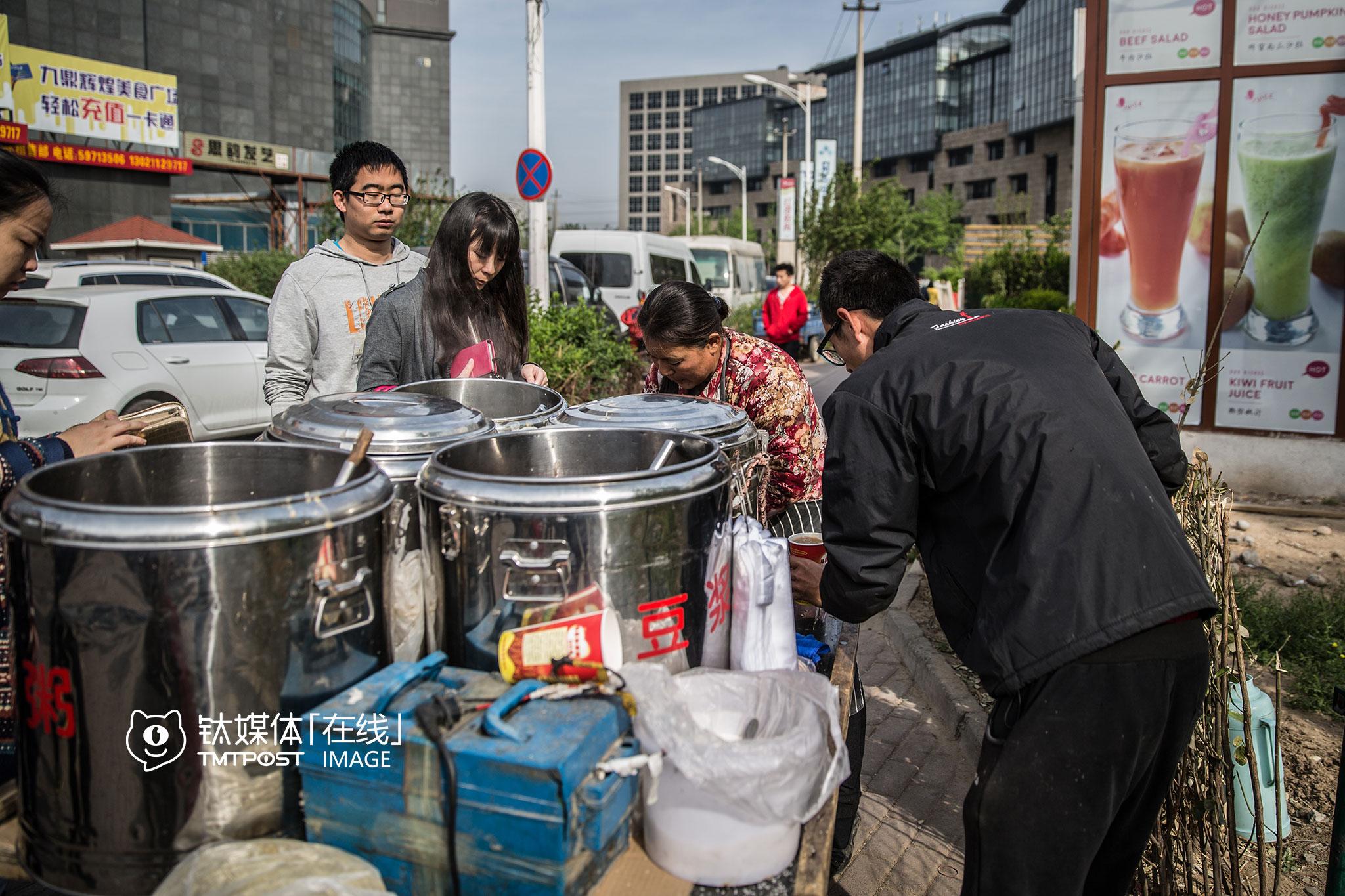 """一对在路口卖粥的母子,他们在上地卖粥卖了3年,每天就靠早上1个小时做这项生意,""""每天早上卖100杯左右,必须动作快,在这里上班的人,没时间和耐心等。"""""""