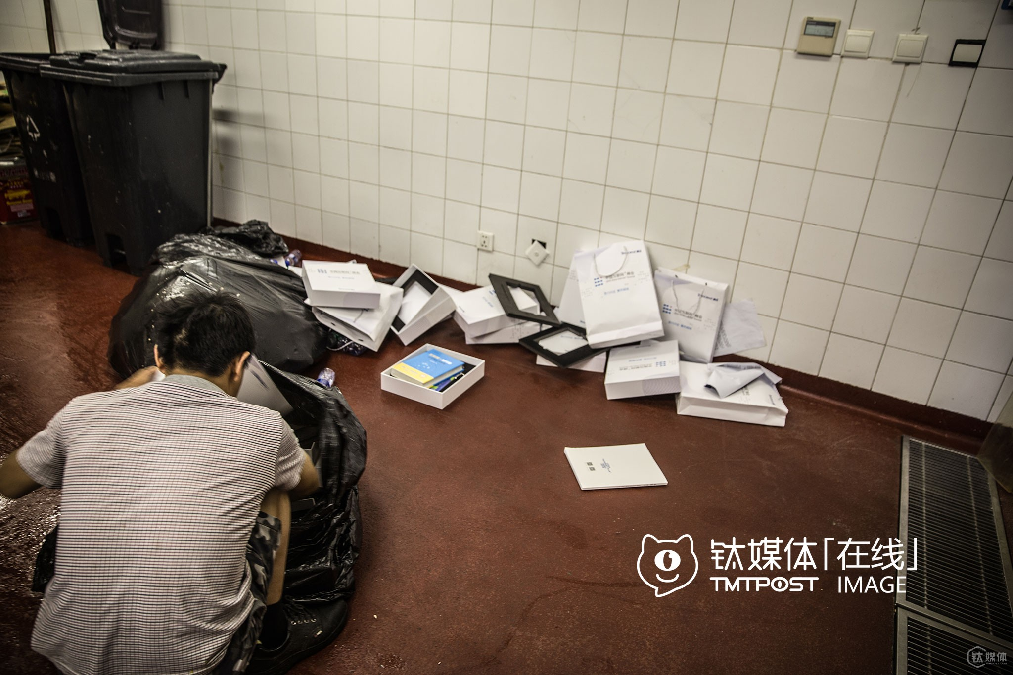 "It was the B2 junk room of China World Trade Center Tower 3, Beijing. After an innovation conference ended, the building cleaner collected lots of paper bags, gifts from the venue. ""There are lots of books, but they are meaningless because I can't understand them. I shall sell all these stuffs to the garbage man who's to arrive soon,"" he explained."