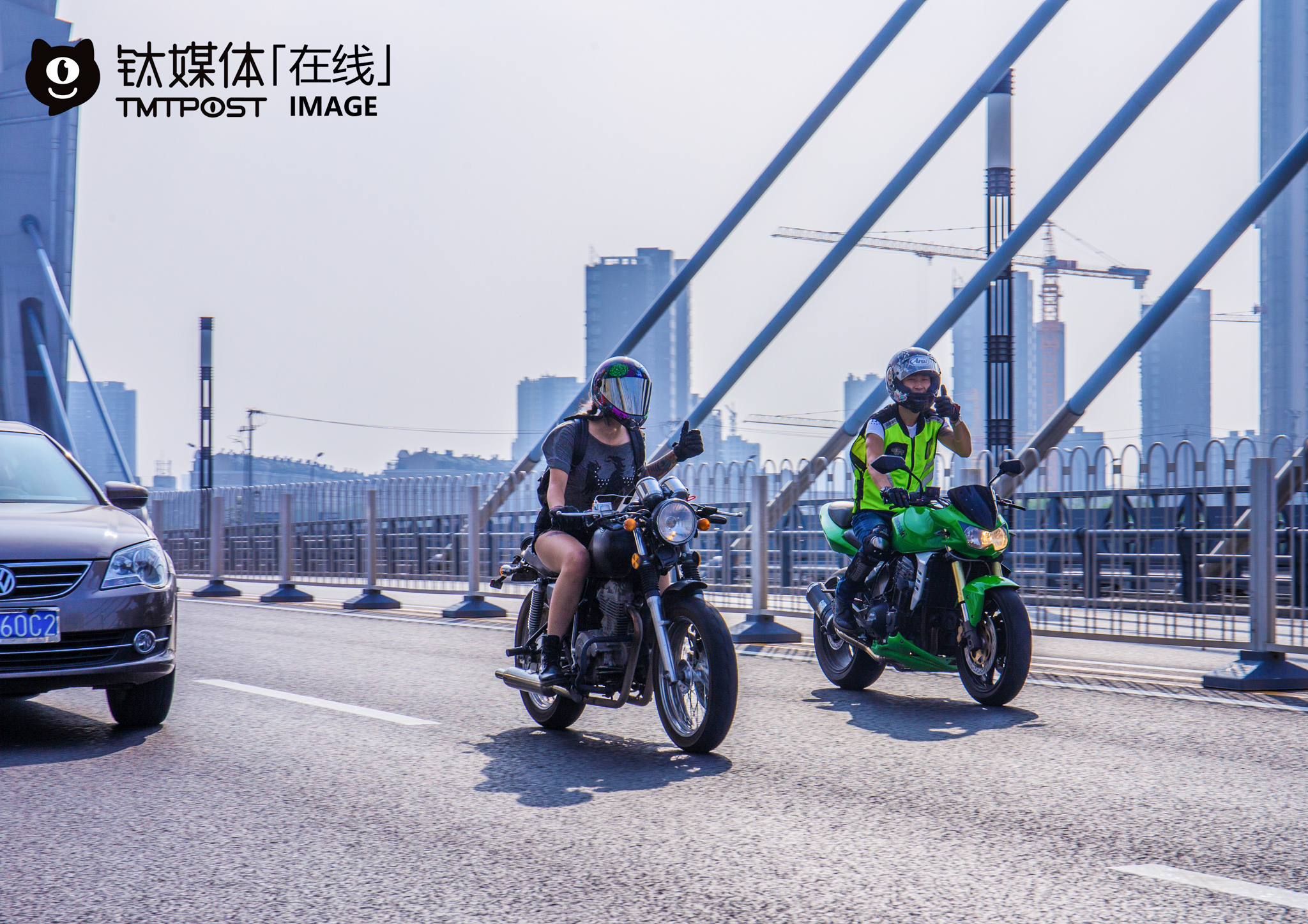"""Bu Yi (the motorcycle rider to the right of the picture) was riding on the Tongzhou north Tunnel Bridge, and showing his greetings to another motorcycle rider he encountered on the road. """"If other motorcycle riders found that I didn't wear protective clothing or ride on the wrong road, they would approach and barge me,"""" he explained. For him, strict intendance among motorcycle riders will not only improve our safety awareness, but also improve the riding environment for motorcycle riders, and this is what he referred to as the """"rider spirit"""". According to transportation rules in Beijing, riders could ride motorcycles with Beijing-A plate inside Beijing, but they could not ride motorcycles with Beijing-B plate inside the fourth ring."""