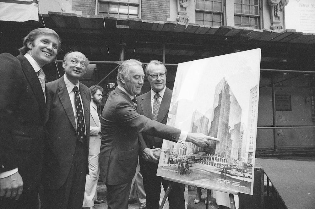 时任纽约州长休·凯瑞(Hugh Carey)指着海军准将酒店旧址上将建成的新君悦酒店,拍摄于1978年6月28日,照片中人物从左至右依次为特朗普、时任纽约市长郭德华(郭德华)和凯瑞 AP Photo